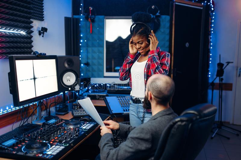 Sound operator and female singer, recording studio. Sound operator and female singer at remote control panel in audio recording studio. Musician at the mixer stock image