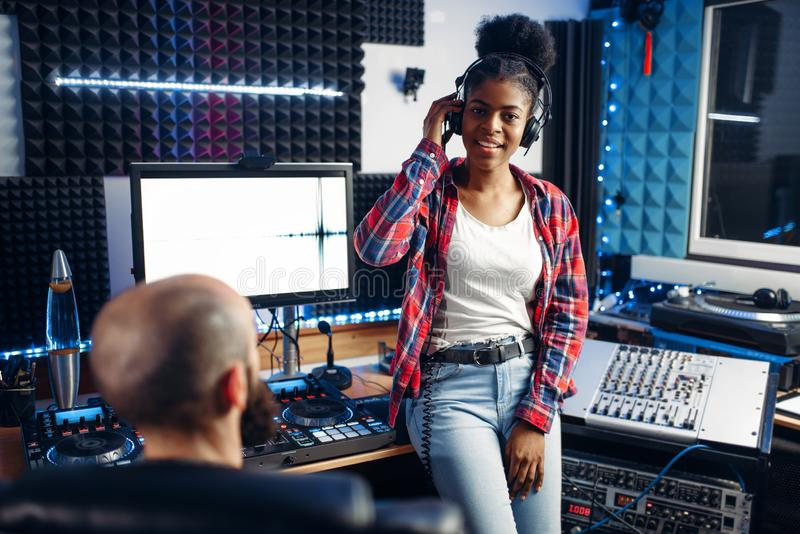 Sound producer and female performer in studio. Sound producer and female performer in headphones listens composition in recording studio. Professional audio and stock images