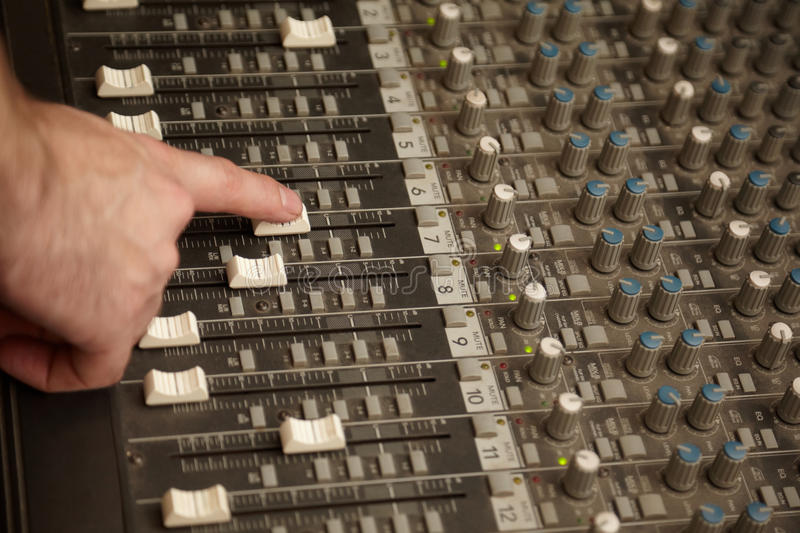 Sound producer moving fader of dusty sound mixer. Sound producer moving one fader of dusty sound mixer stock image