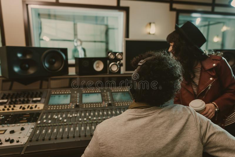 sound producers looking at singer stock photo