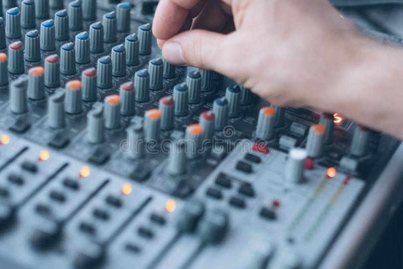 Sound recording audio production studio man. Sound recording and audio production studio. Closeup of man hand mixing tracks, adjusting tune effects royalty free stock image