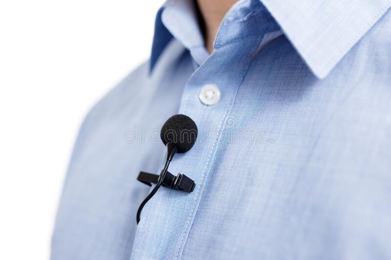 Sound recording concept - close up of small lavalier clip-on microphone on male shirt royalty free stock photography