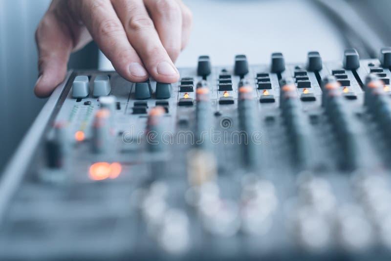 Sound recording studio audio mixer tune effects. Sound recording studio. Closeup of man hand using professional audio mixer to adjust tune effects royalty free stock photography