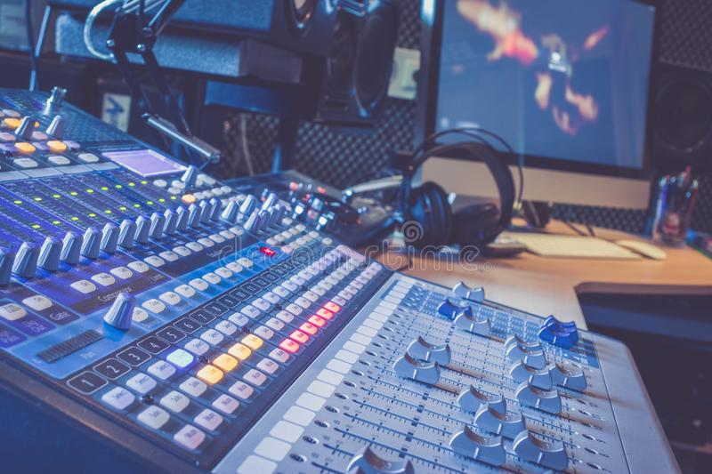 Sound recording studio mixer desk: professional music production, equipment in the blurry background royalty free stock image