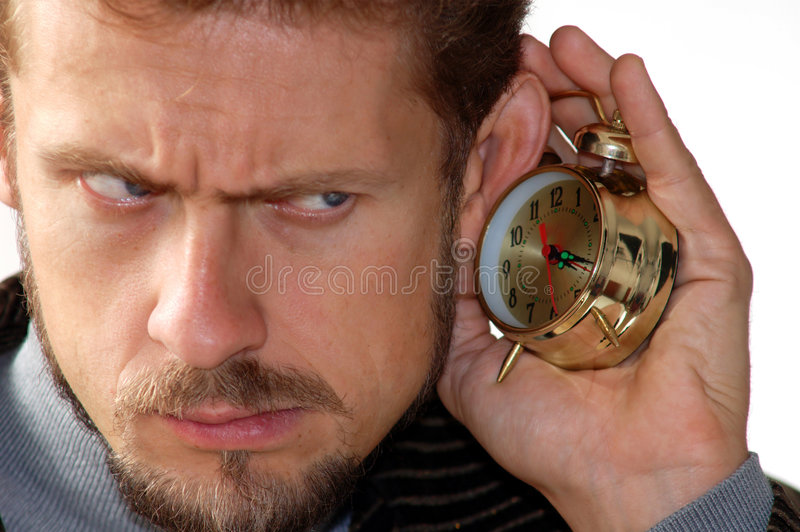Sound-watch. A man listening to an alarm clock sound stock photo