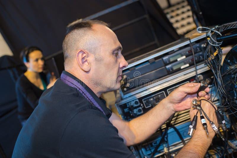 Soundman som förbinder upp utrustning fotografering för bildbyråer