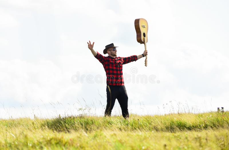 Sounds Like Music. western camping and hiking. hipster fashion. happy and free. sexy man with guitar in checkered shirt. Cowboy man with acoustic guitar player royalty free stock photo