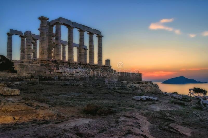 Sounion Attica/Grekland: Den färgrika solnedgången på udde Sounion och fördärvar av templet av Poseidon royaltyfri foto