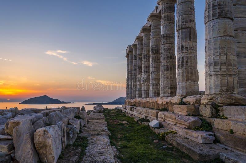 Sounion Attica/Grekland: Den färgrika solnedgången på udde Sounion och fördärvar av templet av Poseidon arkivfoton