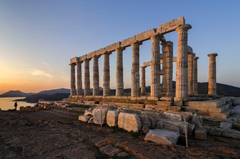Sounion Attica/Grekland: Den färgrika solnedgången på udde Sounion och fördärvar av templet av Poseidon royaltyfria foton