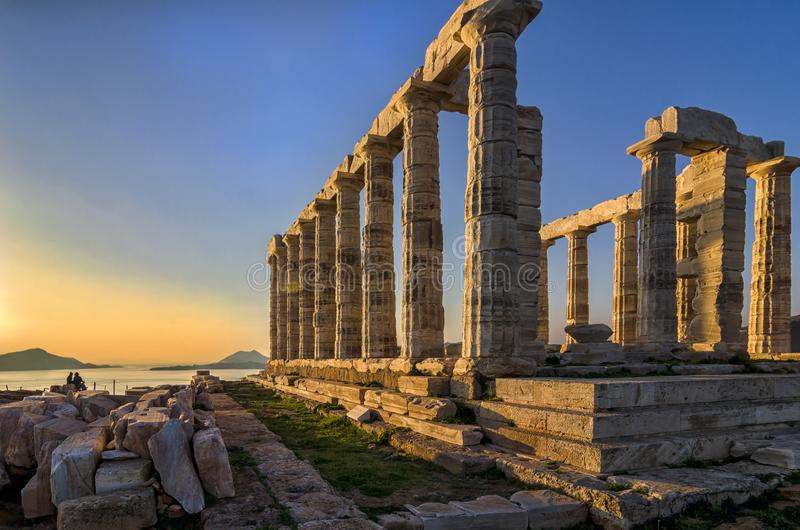 Sounion Attica/Grekland: Den färgrika solnedgången på udde Sounion och fördärvar av templet Poseidon med den synliga Patroklos ön royaltyfri fotografi