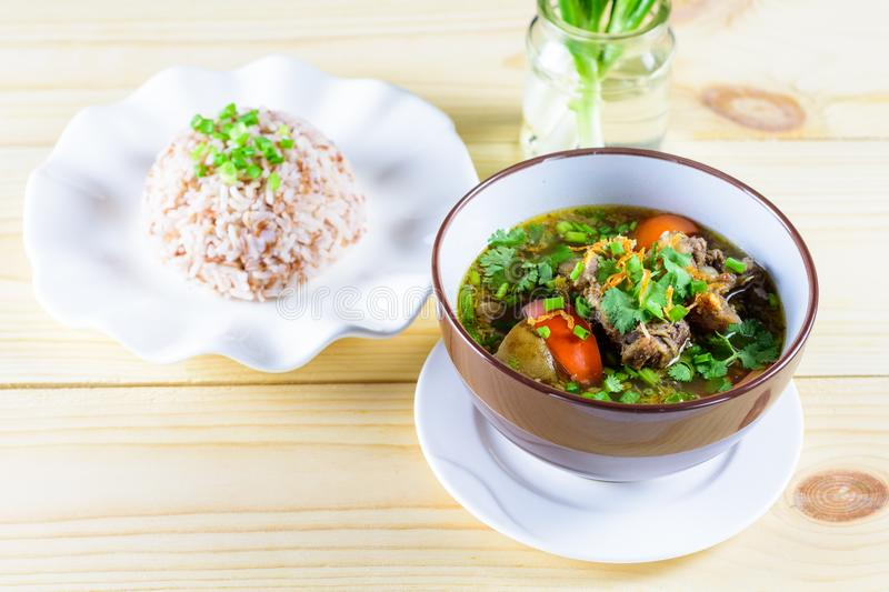 Soup with beef, vegetables, bone broth as base and boiled rice. On wood table stock image
