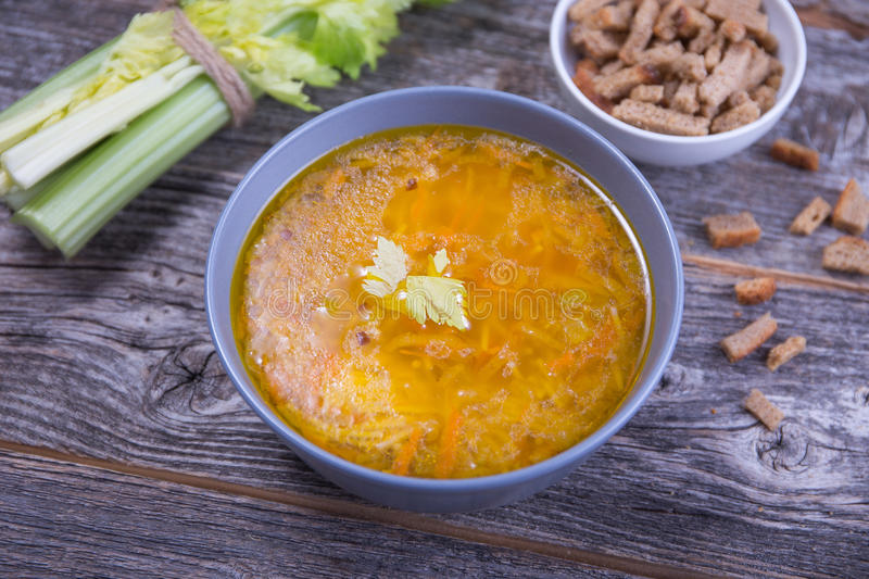 Soup bowl of chicken stock with noodles, carrots and chive royalty free stock photography
