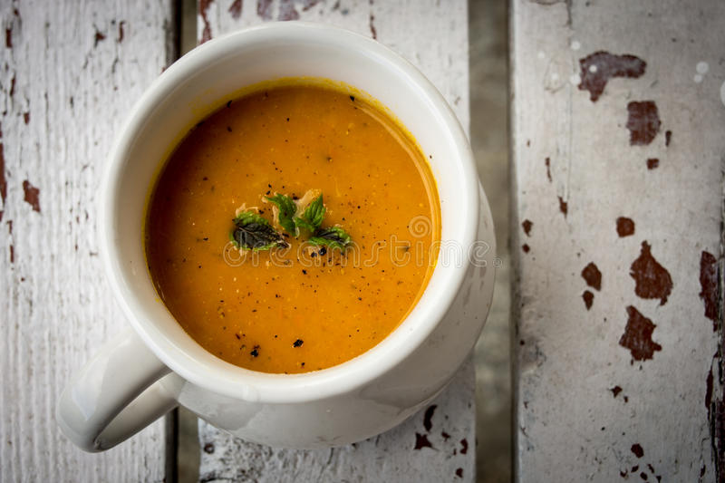 Soup with carrots, ginger and orange juice decorated with mint seen from above.  stock photos