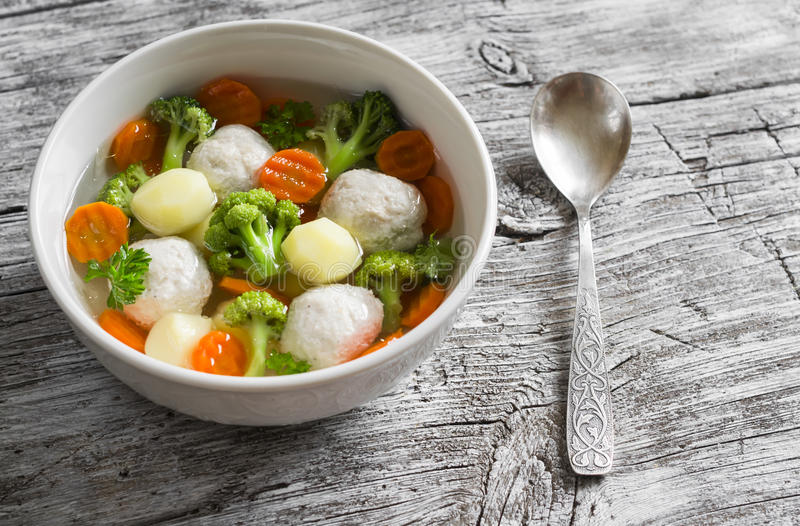 Soup with chicken meat balls, potatoes, broccoli and carrots in a white bowl stock image
