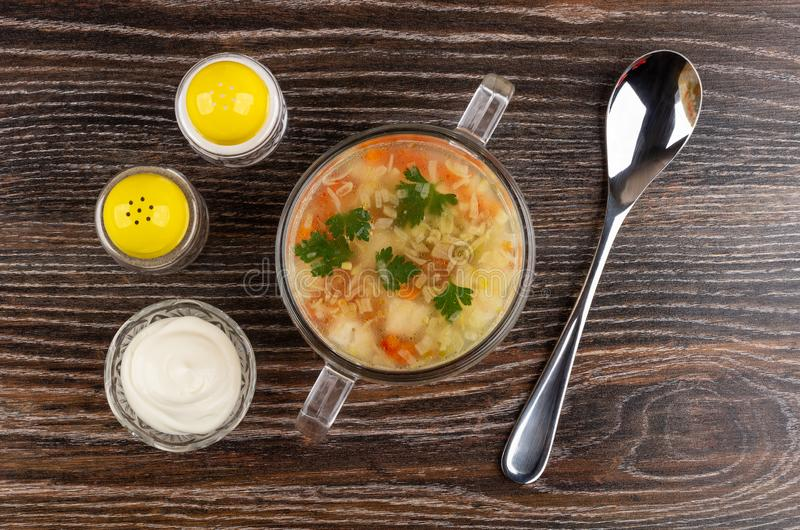 Soup with chicken meat, rice, vegetables in bowl, salt and pepper, bowl with mayonnaise, spoon on table. Top view royalty free stock photography