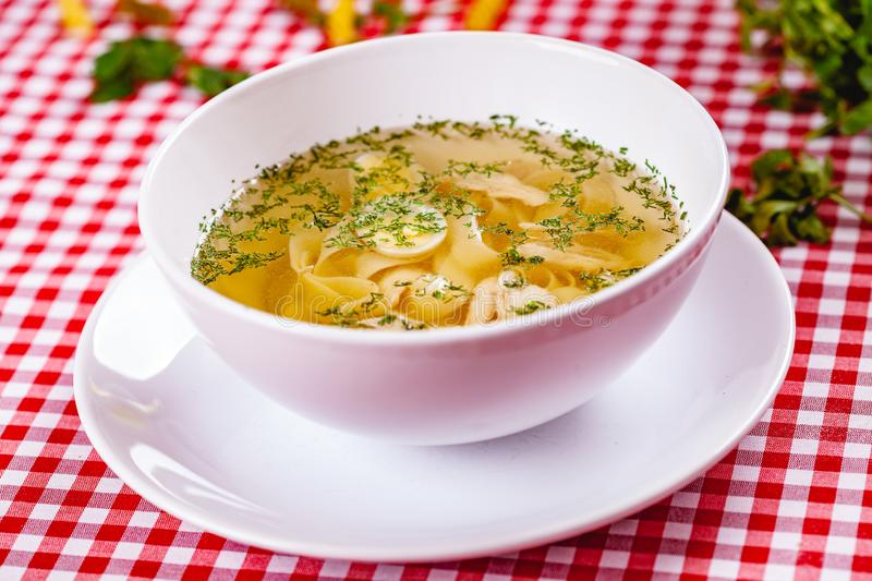 Soup with chicken, quail egg and pasta in white bowl. Close up stock photos