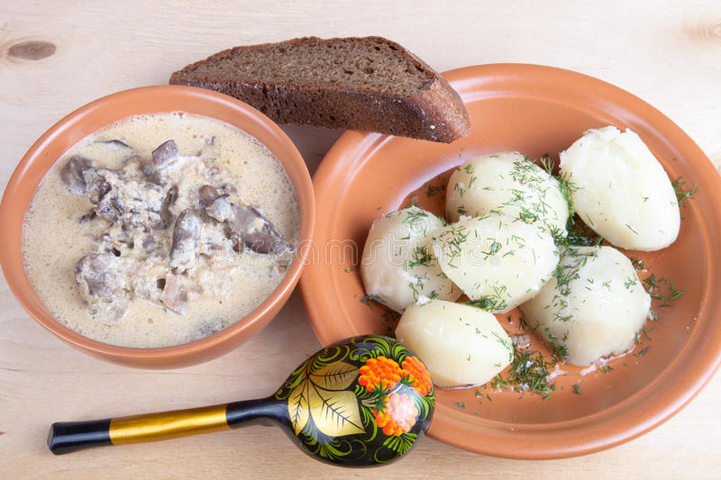 Soup of chiken liver and boiled potato with dill on a wooden boa royalty free stock photo