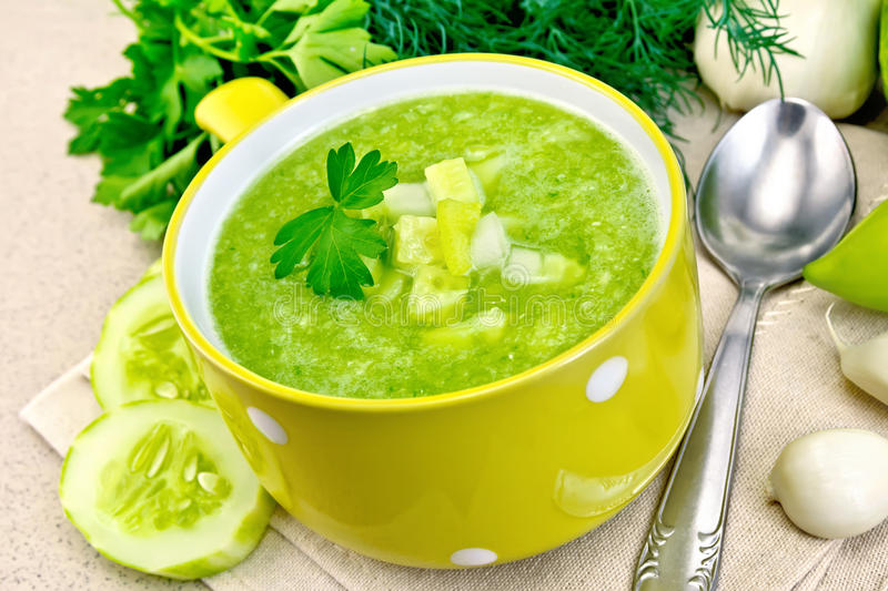 Soup cucumber in yellow bowl on granite table royalty free stock image