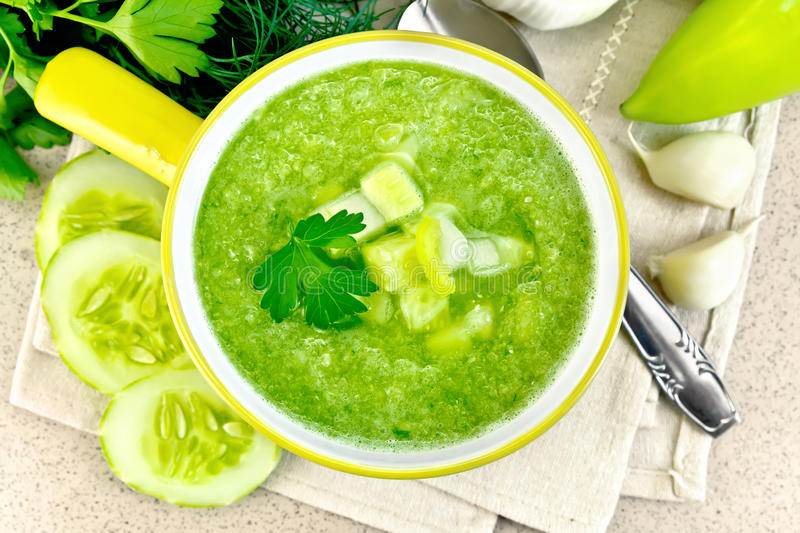 Soup cucumber in yellow bowl on granite table top royalty free stock photos