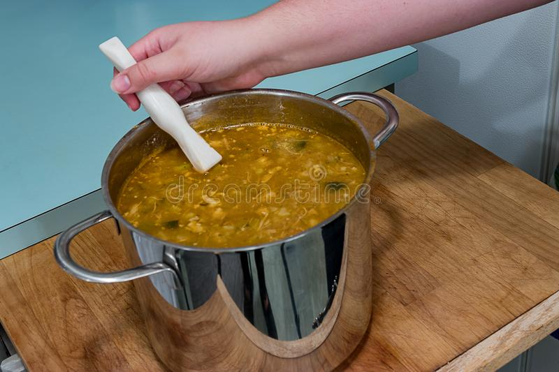 Soup on cutting board. Hand stirring pot of soup on cutting board stock photos
