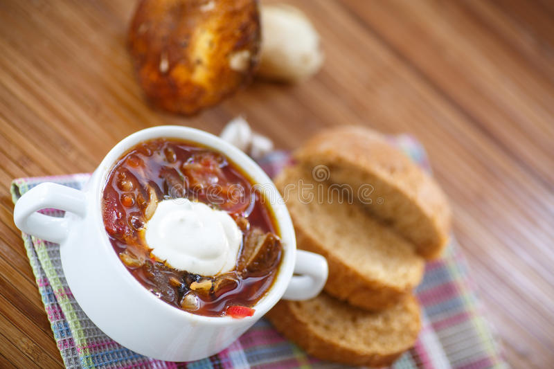 Soup with mushrooms. In a bowl on a wooden table stock photography