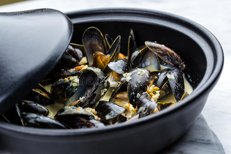 Soup of mussels creamy. Soup of mussels creamy in black bowl on marbel surface stock photos