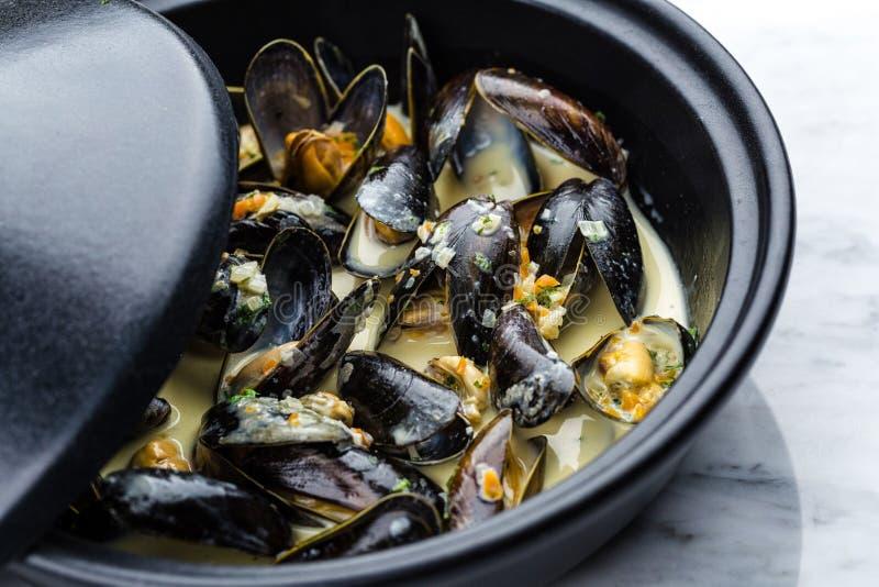Soup of mussels creamy. Soup of mussels creamy in black bowl on marbel surface stock image