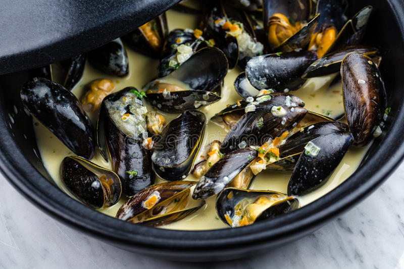Soup of mussels creamy. Soup of mussels creamy in black bowl on marbel surface royalty free stock photography