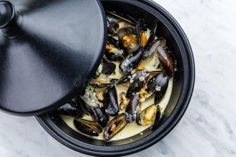 Soup of mussels creamy. Soup of mussels creamy in black bowl on marbel surface stock photo