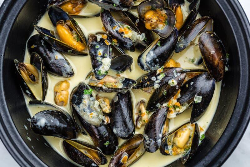 Soup of mussels creamy. Soup of mussels creamy in black bowl on marbel surface royalty free stock image