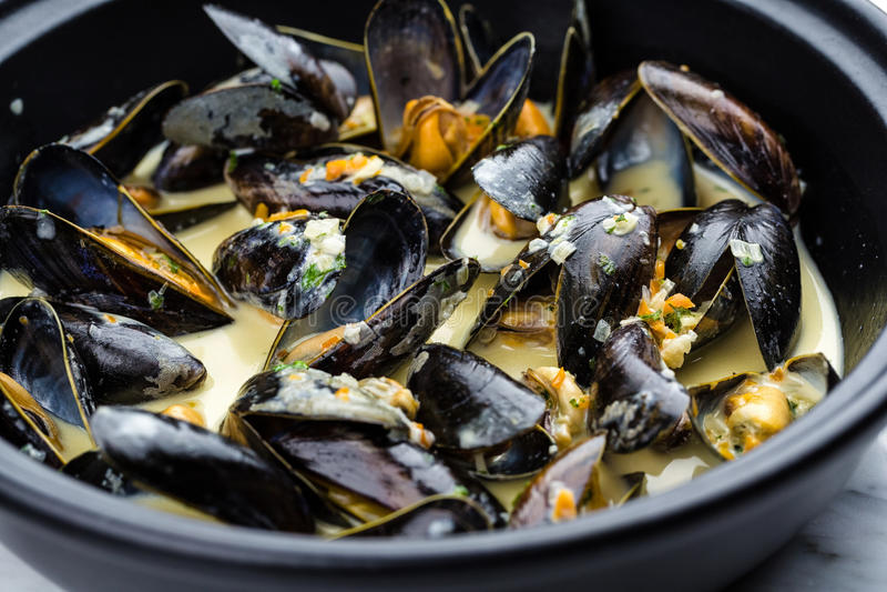 Soup of mussels creamy. Soup of mussels creamy in black bowl on marbel surface royalty free stock photo