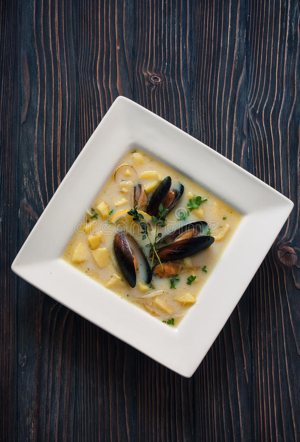 Soup with mussels and potatoes. Cream- soup with mussels and potatoes it white plate over dark wood background. Top view royalty free stock photos