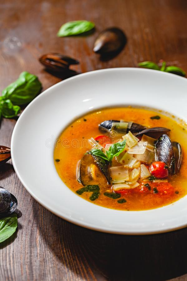 Soup with mussels and vegetables in white plate on wooden table. Close up royalty free stock photography
