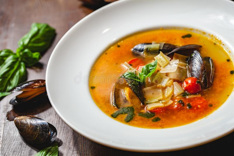 Soup with mussels and vegetables in white plate on wooden table. Close up royalty free stock image