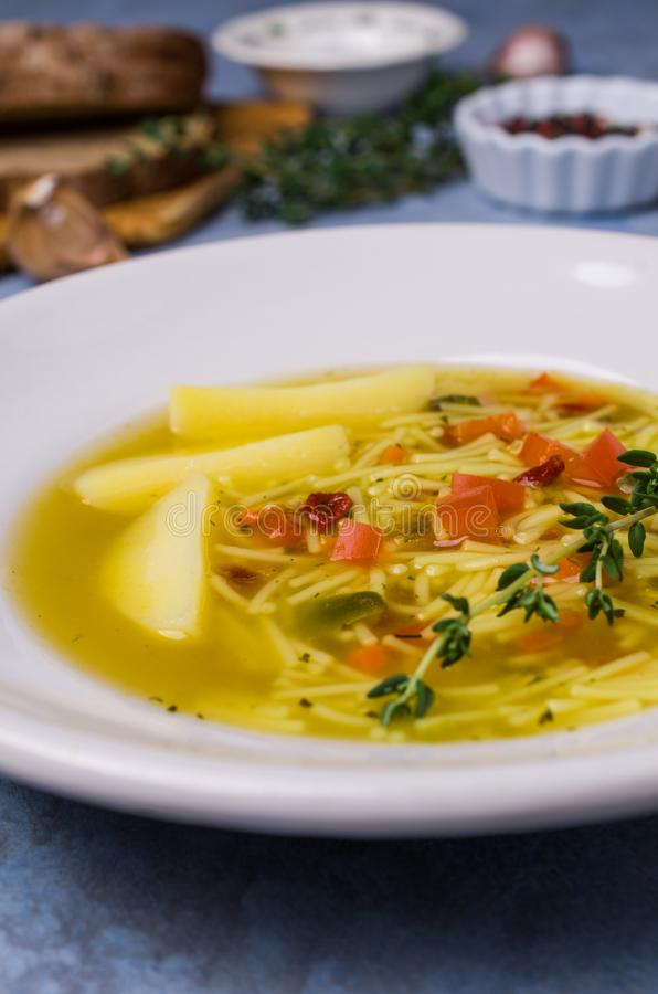 Soup with pasta and vegetables. In bowl on stone background. Selective focus royalty free stock images