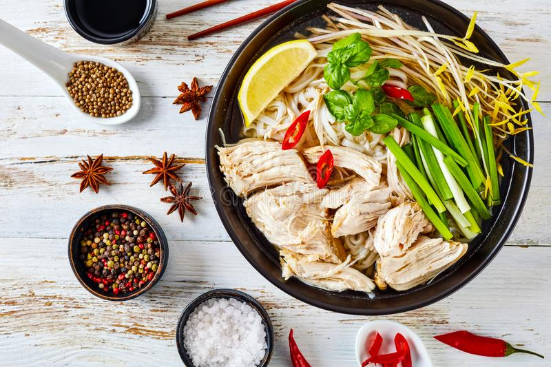 Soup Pho Ga with chicken breast, flatlay. Soup Pho Ga with chicken breast, rice noodles, bean sprouts, spices and fresh herbs in an earthenware bowl, vietnamese royalty free stock images