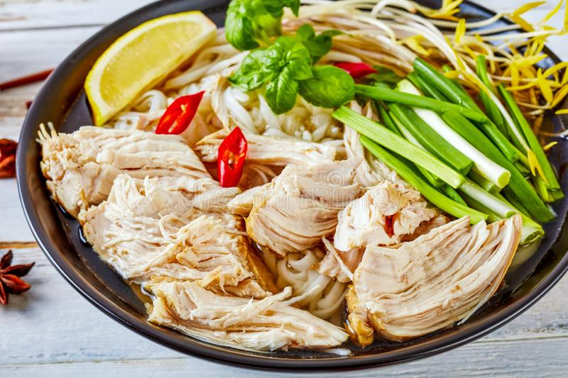 Soup Pho Ga with chicken breast, rice noodles. Close-up of vietnamese soup Pho Ga with chicken breast, rice noodles, bean sprouts, spices and fresh herbs in an stock images