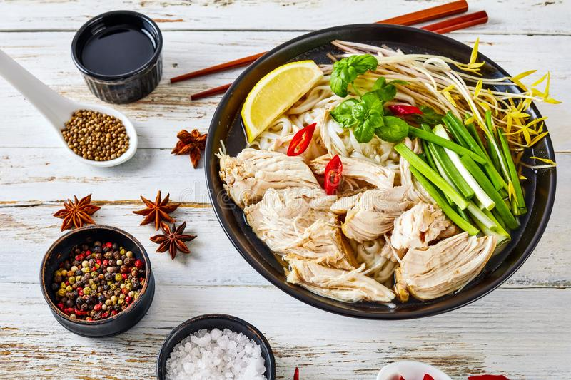 Soup Pho Ga with chicken breast, rice noodles. Bean sprouts, spices and fresh herbs in an earthenware bowl, vietnamese cuisine, view from above stock image