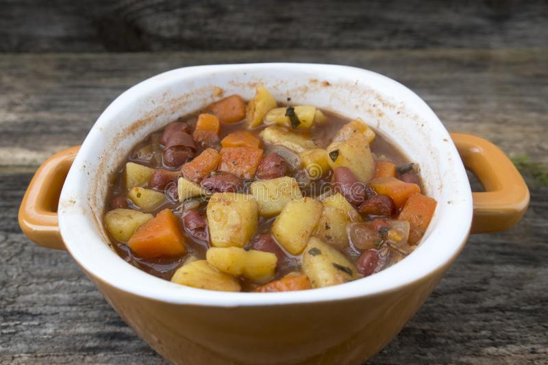 soup with potatoes, onions, carrots and beans stock image