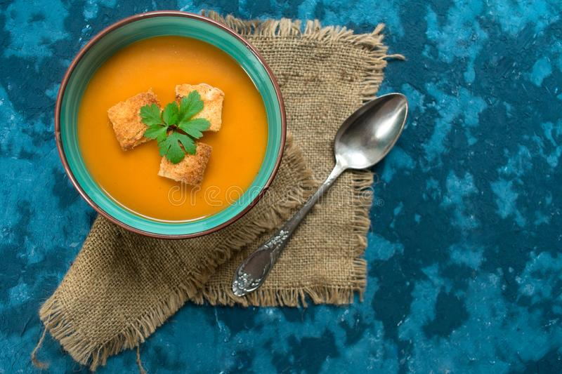 Soup pumpkin puree and small croutons on a blue background. Top view. Autumn menu concept. Copy space. royalty free stock photo
