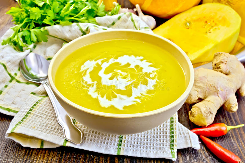 Soup-puree pumpkin with cream in bowl on napkin and board royalty free stock images