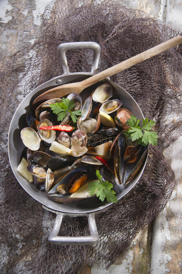 Soup seafood. Preparing a soup made from seafood with garlic and parsley stock images
