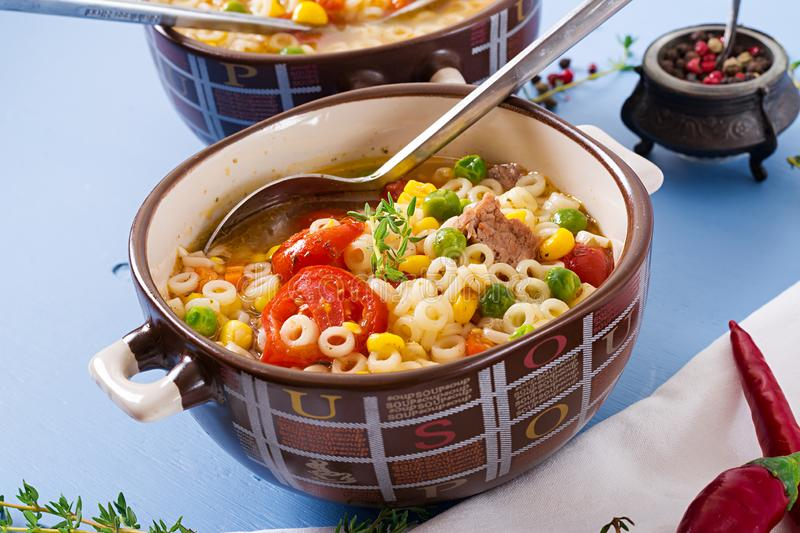 Soup with small pasta, vegetables and pieces of meat in bowl on blue table. Italian food stock photos