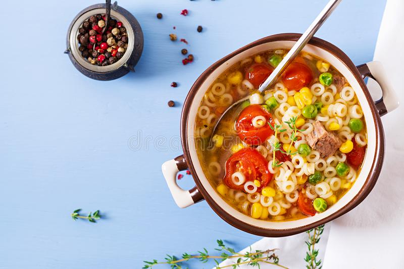 Soup with small pasta, vegetables and pieces of meat in bowl on blue table. Italian food. Top view. Flat lay royalty free stock images