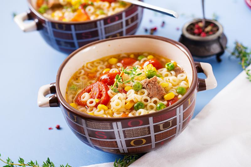 Soup with small pasta, vegetables and pieces of meat in bowl on blue table. Italian food royalty free stock images