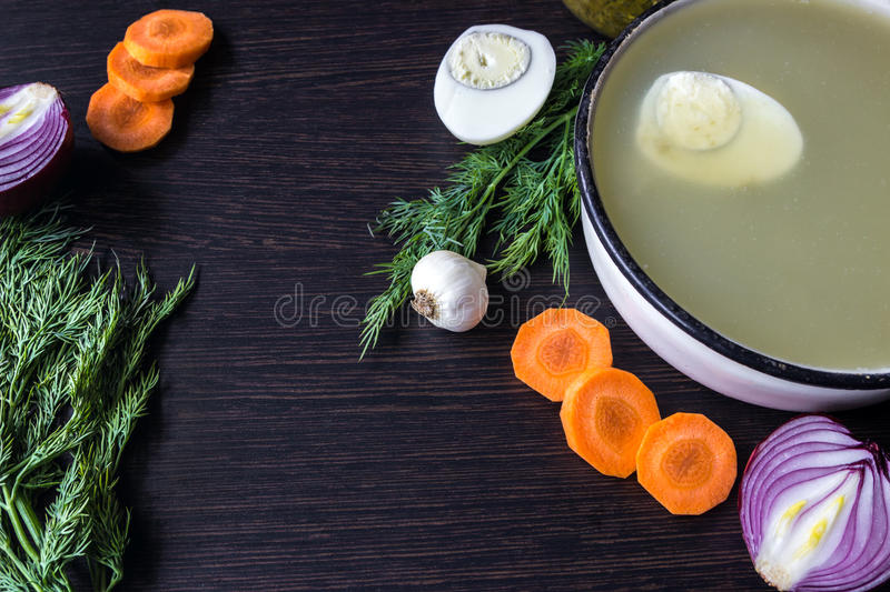 Soup with sorrel, vegetables and boiled egg, red onion, carrots, garlic, dill on dark wooden table. stock image
