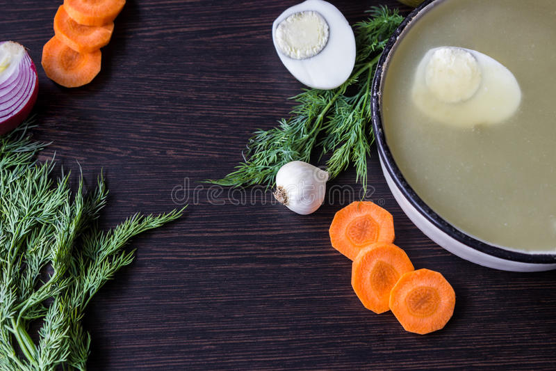 Soup with sorrel, vegetables and boiled egg, red onion, carrots, garlic, dill on dark wooden table. royalty free stock photo