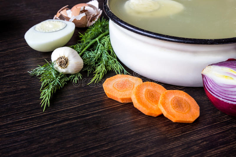 Soup with sorrel, vegetables and boiled egg, red onion, carrots, garlic, dill on dark wooden table. royalty free stock photos