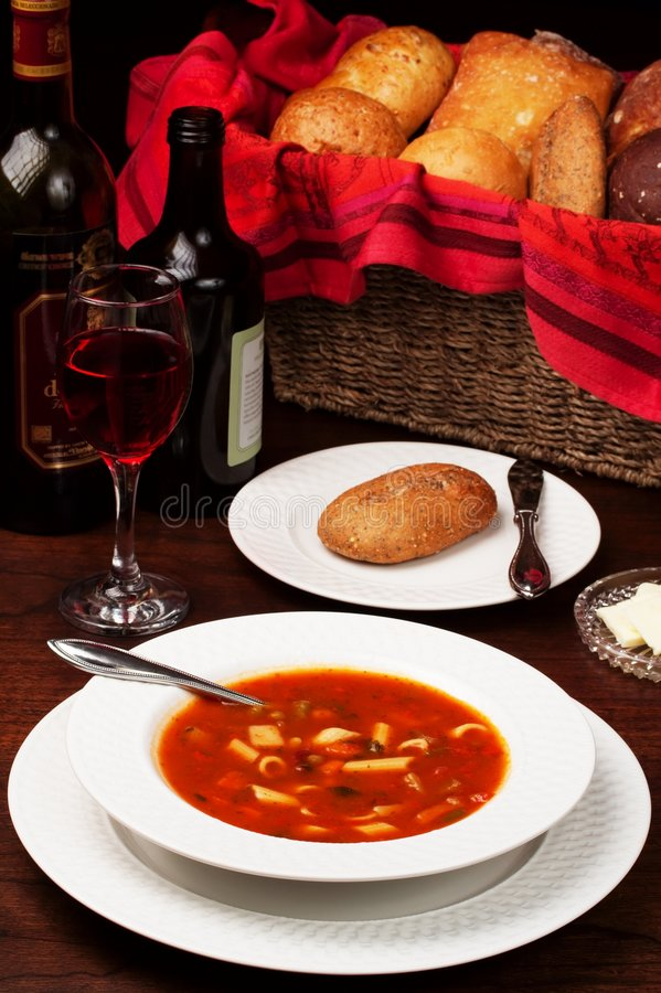 Soup for Supper. An elegant setting of minestrone soup and dinner breads. Bottles of oil and wine and a full wineglass accent the low-key background royalty free stock photo